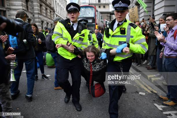 TOPSHOT Police officers remove climate change activists from their road blockades around the Bank of England in the City of London financial district...