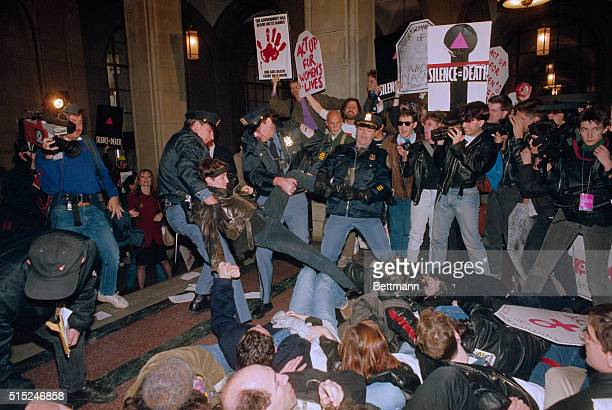 Police officers remove members of ActUp who have staged a sitin inside the hallway of the New York State Capitol in Albany Over one thousand...