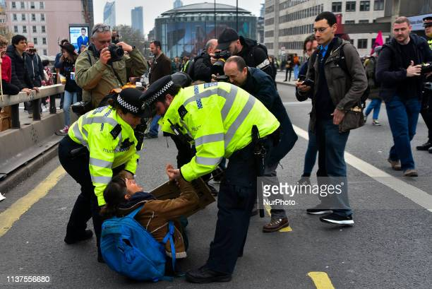 Police officers remove protesters from a blockade on Waterloo Bridge during the second day of a coordinated protest by the Extinction Rebellion group...