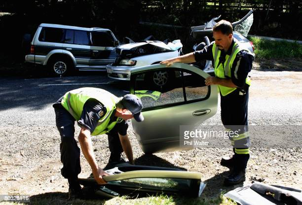 Police officers remove wreckage from the scene where four people were killed in a road accident near Clevedon March 21 2008 in Auckland New Zealand...