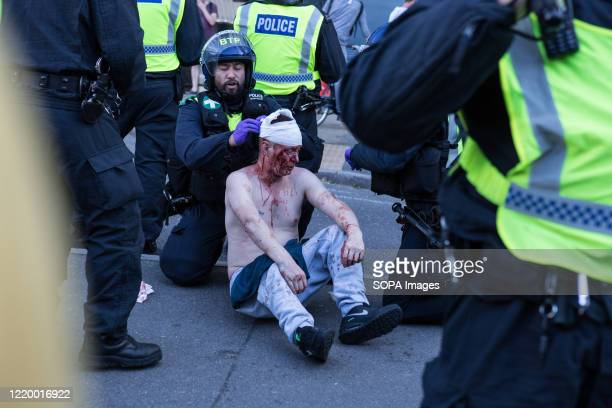 Police officers rescue a man who was attacked by the Black lives matter protesters during the demonstration. Groups including the far-right activists...