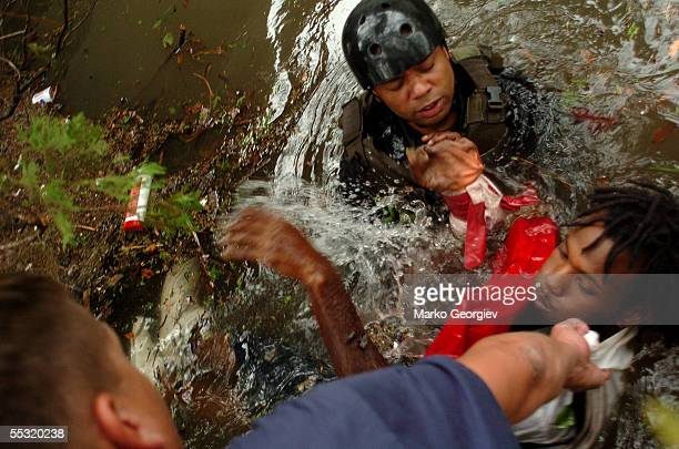 Police officers rescue a unidentified person from the flooded Lower Ninth Ward in New Orleans, Louisiana on August 29, 2005. Hurricane Katrina...