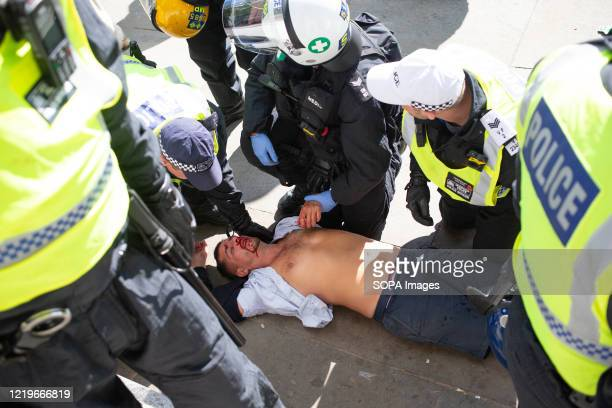 Police officers rescue an EDL supporter who was attacked by the Black lives matter protesters in Trafalgar square during the demonstration. The death...