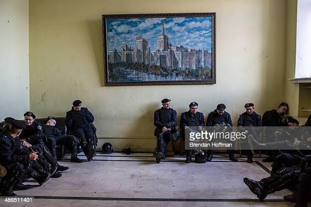 Police officers rest inside the regional administration building as people protest outside on April 24 2014 in Kharkiv Ukraine The legislative body...