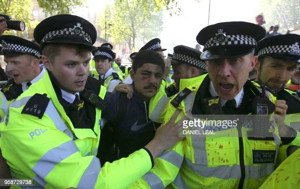 Police officers restrain a demonstrator during a protest against Turkey's President Recep Tayyip Erdogan outside the entrance to Downing Street in...