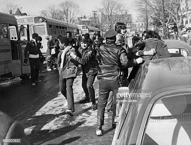 Police officers restrain a white student and a black student after fighting broke out at Hyde Park High School in Boston when buses were about to...