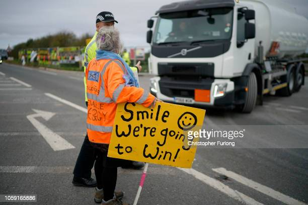 Police officers restrain an antifracking protester attempting to stop a tanker lorry leaving the Preston New Road drill site where energy firm...