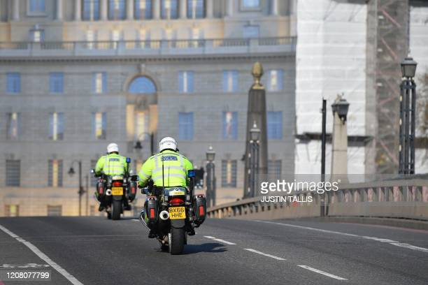 Police officers ride across Lambeth Bridge in central London in the morning on March 24 2020 after Britain ordered a lockdown to slow the spread of...