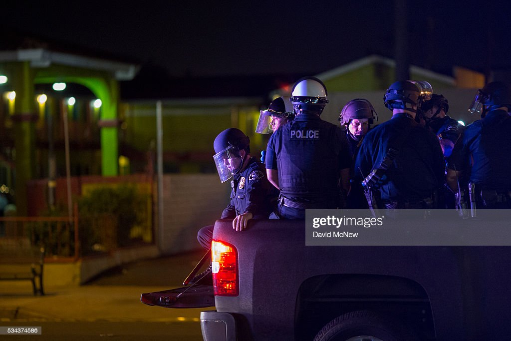 Police officers ride in the back of a pickup truck after forcing protesters down the street under threat of arrest following after a campaign rally by presumptive GOP presidential candidate Donald Trump at the Anaheim Convention Center earlier in the day on May 25, 2016 in Anaheim, California. Previous visits by the candidate to Orange County have sparked protests that resulted in some arrests. The presidential candidates are campaigning in Southern California for the June 7 California primary.