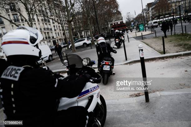 Police officers ride their motorbikes in the streets of Paris during a demonstration called by the yellow vests movement to protest against the...