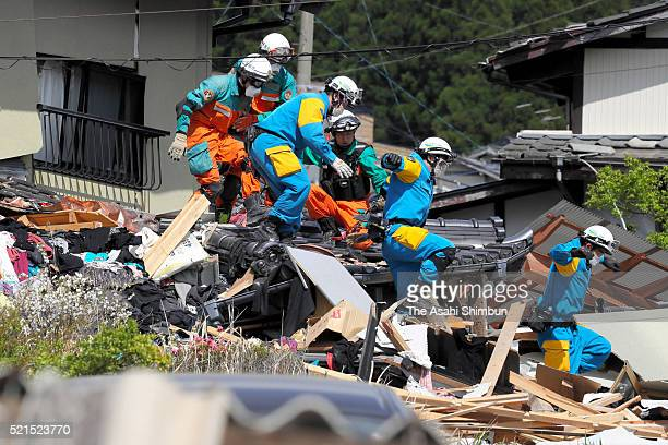 Police officers run on the debris as an earthquake warning is issued while rescue operation continues on April 16 2016 in Minamiaso Kumamoto Japan...