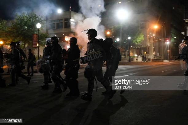 Police officers run through Jefferson Square Park in downtown Louisville, Kentucky, on September 23 as protestors react after a judge announced the...
