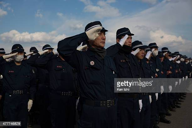 Police officers salute during 3rd anniversary ceremony on March 10 2014 in Fukushima Japan On March 11 Japan commemorates the third anniversary of...