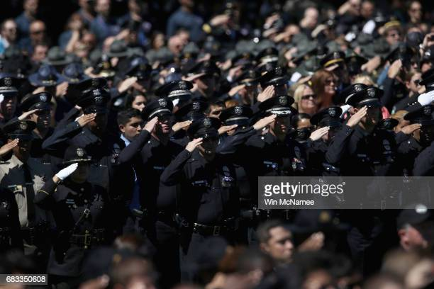 Police officers salute during the 36th annual National Peace Officers' Memorial Service at the US Capitol on May 15 2017 in Washington DC The service...