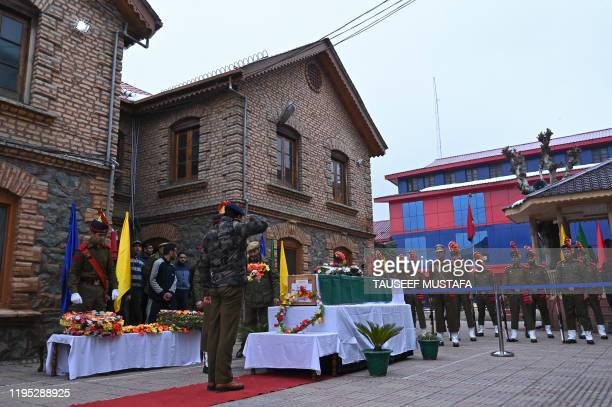 Police officers salute in a wreath laying ceremony in front of the coffin of a slain colleague following a gun battle between suspected militants and...