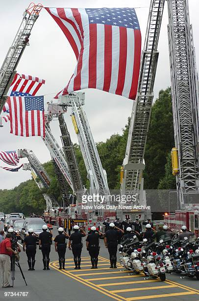 Police officers salute under flags waving from FDNY ladder trucks as motorcade arrives at Calverton National Cemetery in Calverton NY for funeral...