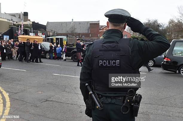 A police officers salutes as the funeral of murdered prison officer Adrian Ismay takes place on March 22 2016 in Belfast Northern Ireland Mr Ismay...