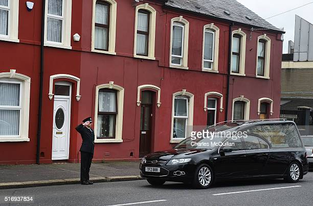 A police officers salutes the hearse on arrival at Woodvale Methodist Church as the funeral of murdered prison officer Adrian Ismay takes place on...