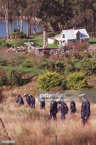 Police officers scour for evidence in a line search near the Seascape Guesthouse where gunman Martin Bryant was apprehended after shooting and...