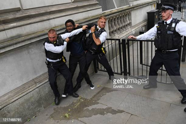 Police officers scuffle with a protestor near the entrance to Downing Street, during an anti-racism demonstration in London, on June 3 after George...