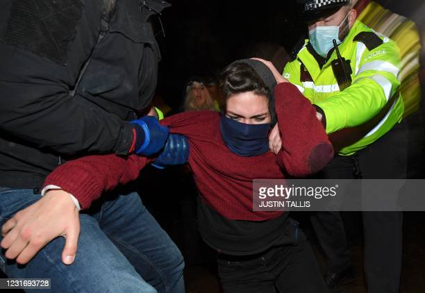 Police officers scuffle with people gathering at a band-stand where a planned vigil in honour of alleged murder victim Sarah Everard was cancelled...