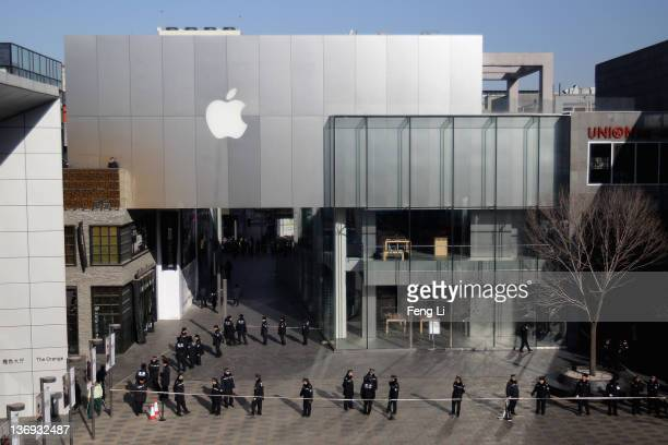 Police officers seal off the area near Apple's Beijing flagship store on January 13 2012 in Beijing China Chinese angry crowd shouted and threw eggs...