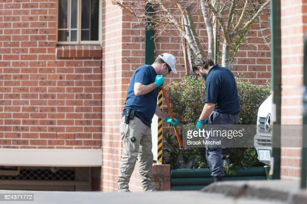 Police officers search a garden bed of an apartment complex in Sproule Street Lakemba the scene of an overnight terror raid on July 30 2017 in Sydney...