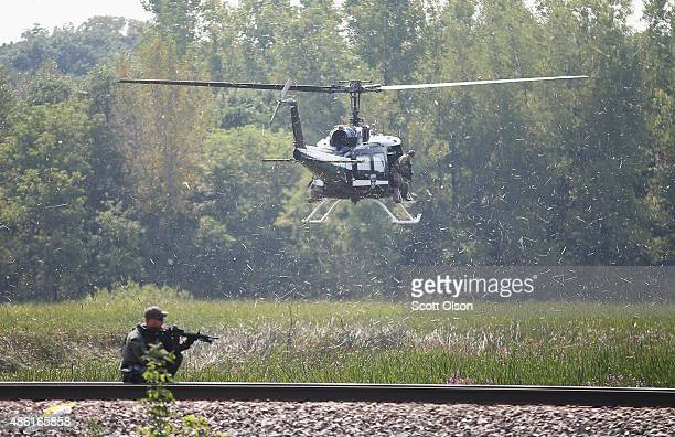 Police officers search an area for suspects involved in shooting an officer September 1, 2015 in Fox Lake, Illinois. A manhunt for three suspects is...