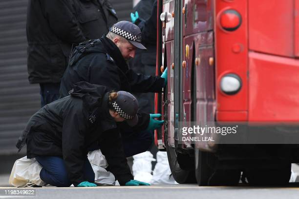 Police officers search around a red London bus on Streatham High Road in south London on February 3 after a man was shot dead by police on February...