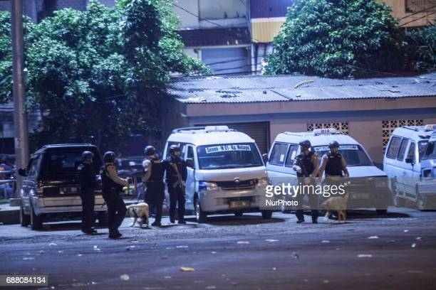 Police officers search for dangerous material in the site of bomb exploison at Kampung Melayu bus station Jakarta Indonesia on May 24 2017 Five...