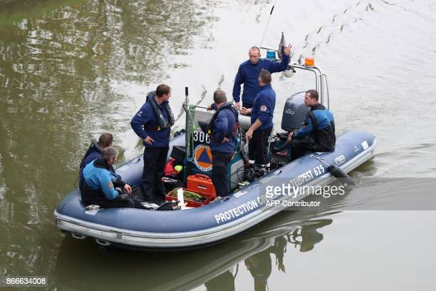 Police officers search for evidences about the1980s Brabant killings case along the canal Brussels Charleroi in Ronquieres on October 26 2017 The...