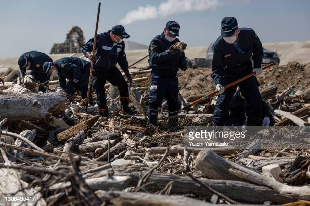 Police officers search for the remains of people who went missing after the 2011 earthquake and tsunami on March 11, 2021 in Namie, Japan. Japan will...