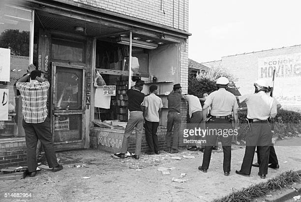 Police officers search men accused of looting during race riots in Detroit Michigan