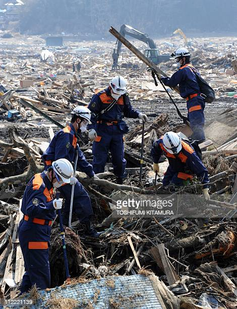 Police officers search missing people among March 11 tsunami debris at the Otomo area in Rikuzentakata city Iwate prefecture on April 15 2011 Japan's...
