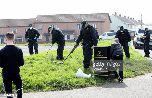 Police officers search waste ground near the scene in the Creggan area of Derry in Northern Ireland on April 20 2019 where journalist Lyra McKee was...