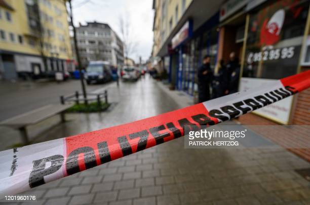 Police officers secure a crime scene behind a police cordon in front of a bar at the Heumarkt in the centre of Hanau near Frankfurt am Main western...