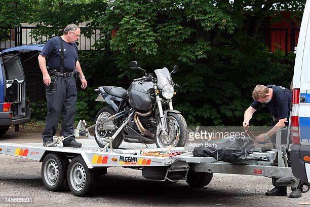 Police officers secure a motorcycle that has been seized at the clubhouse of the motorcycle gang Bandidos Del Este to the back of a police van on...