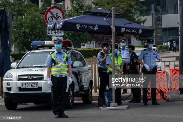 Police officers secure an area before a convoy of buses transporting delegates passes by ahead of the opening ceremony of the Chinese People's...