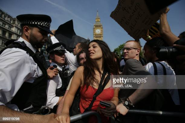 Police officers secure protesters gathered in Parliament Square after marching through London on June 21 during an antigovernment protest to coincide...