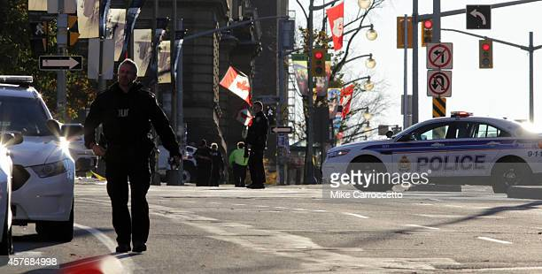 Police officers secure the area near Parliament Hill on October 22 2014 in Ottawa Canada At least one gunman shot and killed a Canadian soldier...