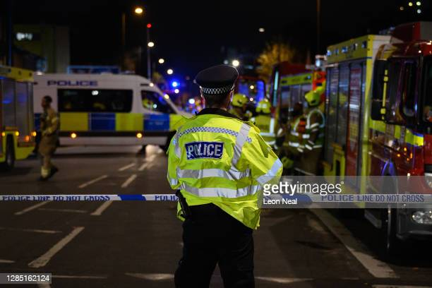 Police officers secure the cordon around Edmonton Green police station, following an incident involving a car colliding with the front doors of the...