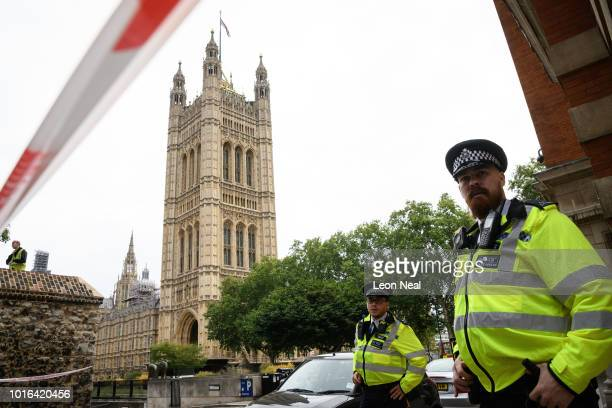 Police officers secure the roads around the Houses of Parliament as forensic teams continue their work around a vehicle after it crashed into...