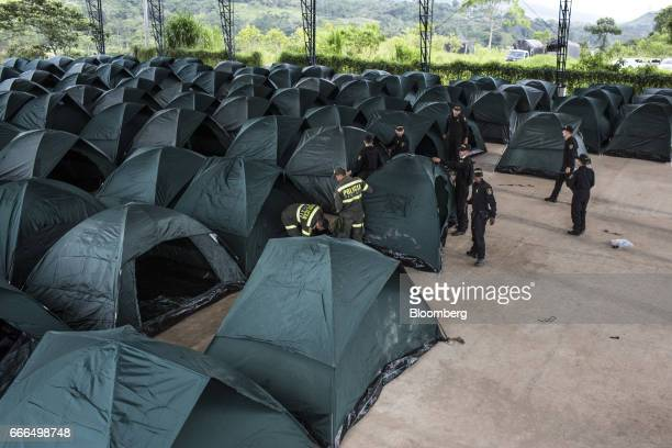 Police officers set up tents at a disaster relief center after landslides in Mocoa Putumayo Colombia on Monday April 3 2017 Torrential rains caused...