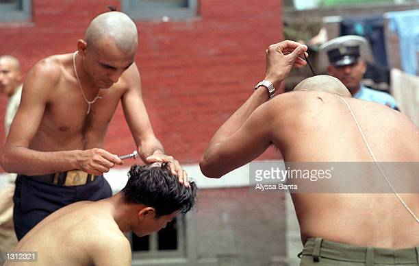 Police officers shave each other''s heads June 3 2001 in the Nepalese capital of Kathmandu as a sign of respect for their king and other members of...