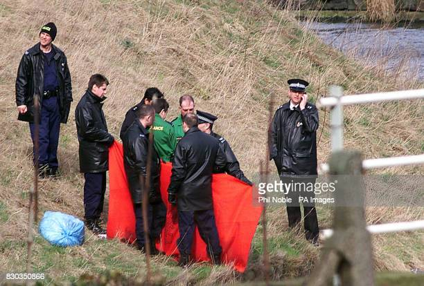 Police officers shield the body of a missing fourmonthold baby girl found by police divers in the LeedsLiverpool canal in Burnley Lancashire A woman...