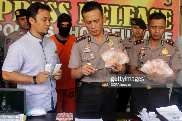 LHOKSEUMAWE ACEH INDONESIA Police officers showed evidence of the arrest of members of two suspected online gambling syndicates between countries...