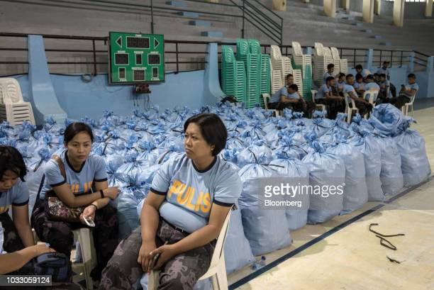 Police officers sit next to bags of relief supplies at a makeshift disaster relief operations center ahead of Typhoon Mangkhut's arrival in...