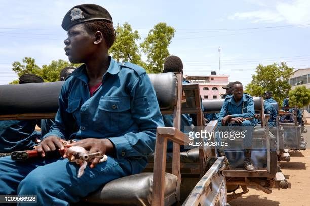 Police officers sit on the back of a pickup truck while they gather ahead of patrolling the streets of Juba, South Sudan on April 9, 2020. - South...