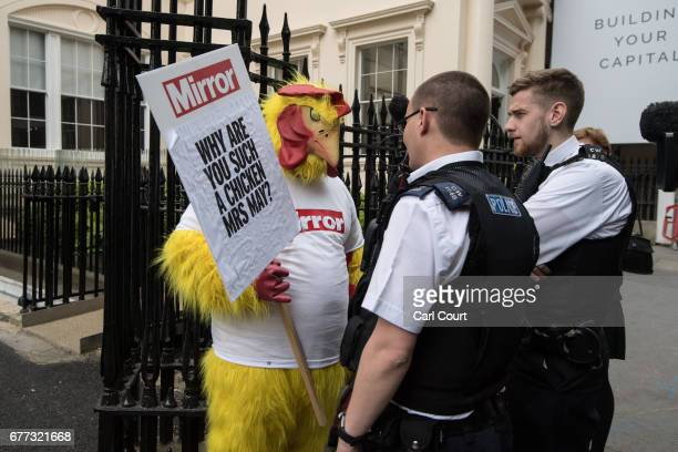 Police officers speak to a Daily Mirror campaigner dressed as a chicken outside a venue where Chancellor of the Exchequer Philip Hammond and...