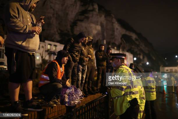 Police officers speak to a group of men standing on a wall as lorry drivers demand the reopening of the Port of Dover on December 22, 2020 in Dover,...